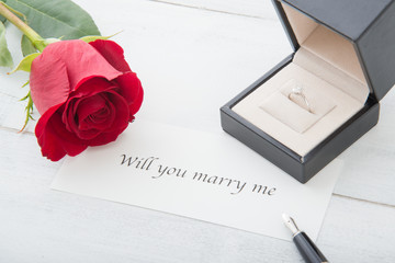 propose message with diamond ring and rose