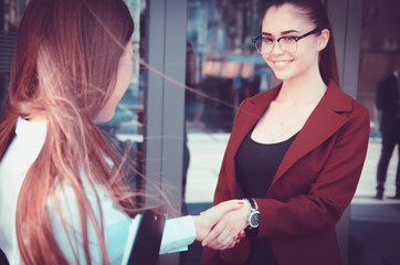 Handshake of two young girls against the background of a multi-storey office building. Make a deal. Friendly relations. Office staff