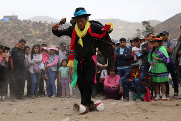 An Andean dancer performs during Day of the Dead celebrations at 'Nueva Esperanza' (New Hope) cemetery in Villa Maria del Triunfo on the outskirts of Lima