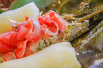 Close up of delicious typical amazonia food, fish cooked in a leaf with yucca and plantain, with salad of tomato and onions, served in a wooden platen over a wooden table