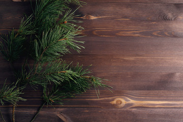 Pine branch on a wooden background. Simple flat lay composition. Minimalistic christmas concept