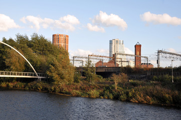 the river aire in leeds taken from the footpath showing the footbridge south back and holbeck with the railway tracks in between