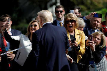 Visitors react as U.S. President Donald Trump poses for a picture as he departs the Oval Office of the White House for Dallas, in Washington D.C.