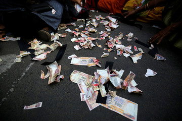Pieces of old fake 1000 rupee notes lay on the street during a protest, organised by India's main opposition Congress party, to mark a year since demonetisation was implemented by Prime Minister Narendra Modi, in Ahmedabad