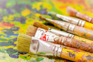 Close up of paint brushes over a color palette in a blurred background