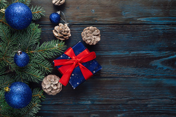 Christmas and Christmas decorations Pine branches of a tree, cones, blue Christmas toys on a wooden background.primary packaging
