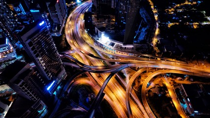 Aerial photography of urban city highway with traffic's light trail at night.