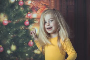 little baby girl near Christmas tree smile