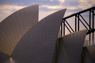Climbers can be seen walking up the arch of the Sydney Harbour Bridge behind the roof of the Sydney Opera House on a hot summer day in Australia