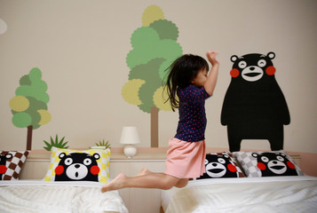 A girl from Singapore jumps on the bed at a quake-resistant dome house decorated with Japan's popular 'Kumamon' bear character after checking in with her family at the Aso Farm Land resort in Aso