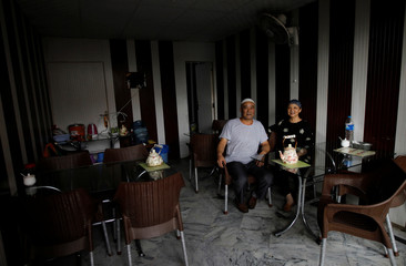 Halima and her husband Saleh pose for a picture in the dining room of the Chinese Muslim restaurant in Islamabad