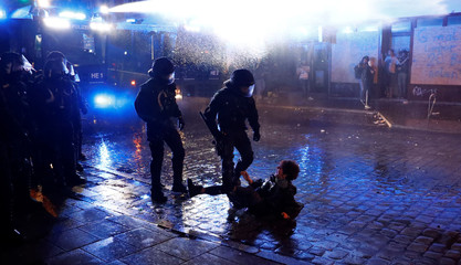 German riot police walk to fallen protester during the demonstration at the G20 summit in Hamburg