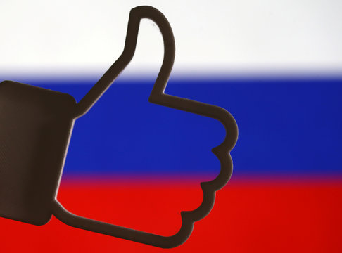 A 3D-printed Facebook like button is seen in front of a displayed Russian flag in this illustration