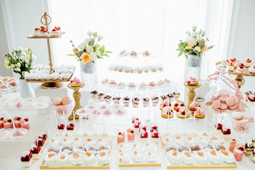 Delicious wedding reception candy bar dessert table full with cakes and sweets and a flower vase with hydrangeas on the background of an exquisite restaurant.