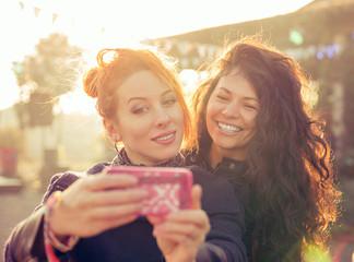 Female friends two women taking selfie having fun during weekend getaway Outdoors