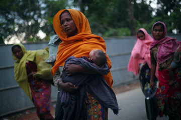 Rohingya refugees, who crossed from Myanmar, walk to a registration centre in Teknaf