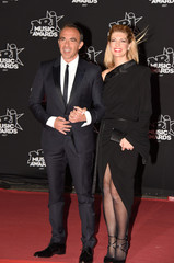 French TV host Nikos Aliagas (L) and his wife Tina Grigoriou pose upon their arrival to attend the NRJ Music Awards ceremony at the Festival Palace in Cannes