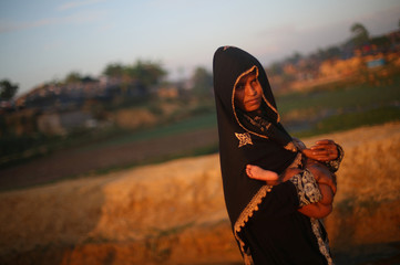 Rohingya refugee carries her child through Kutupalong refugee camp at sunset near Cox's Bazar
