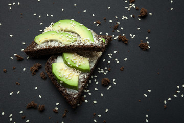 Avocado sandwich with sesame seeds and black bread isolated on a black background.
