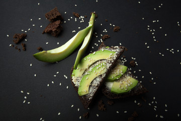 Toast with ripe avocado on a black table. Dietary food.
