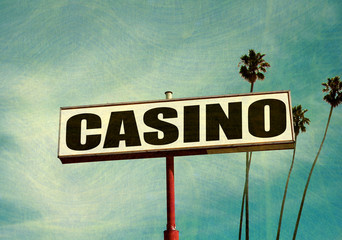aged and worn casino sign with palm trees