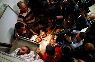 People gather around bodies of Palestinians killed in a tunnel near the border between Israel and central Gaza Strip