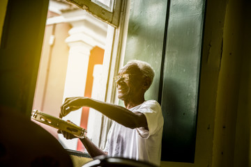 Brazilian senior playing Samba at home