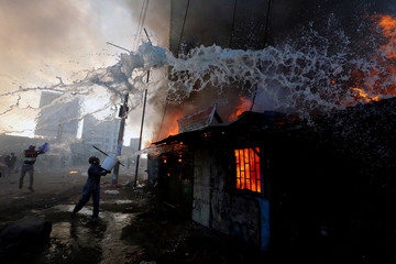 People try to put out a fire at properties set ablaze by rioters in Kawangware slums in Nairobi