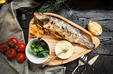 Beautiful grilled fish with lemon on a wooden plate with a glass of white wine on a dark wooden background
