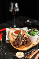 baked lamb on bone with tomato sauce, salad on a wooden plate with a glass of red wine on a dark wooden background