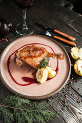 beautiful serving duck leg confit with apples and berry sauce on a wooden plate with a glass of red wine
