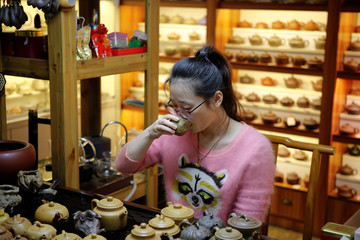 "An owner of a family tea-ware shop drinks tea as handmade red clay pots are seen in the background, in Dingshu town, Yixing city, known as ""pottery city\"