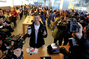 The first customer shows his new iPhone X after buying it at an Apple Store in Beijing