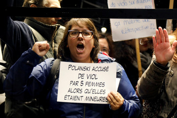 A feminist protester shouts outside the Cinematheque Francaise upon the arrival of director Roman Polanski at an event organised by Cinematheque Francaise in Paris