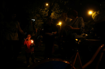A girl holds a candle outside the Instituto Politecnico high school, where the five Argentine citizens who were killed in the truck attack in New York went to school, in Rosario
