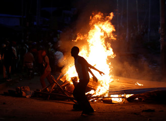 Protesters stand near barricades set on fire by opposition supporters in the slum area of Mathare in the capital Nairobi