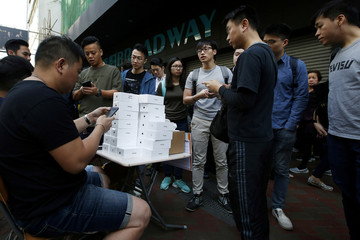 A man pays to buy new iPhone Xs from those who just bought at Apple Stores, on a street in Hong Kong