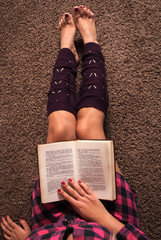 Girl reading book and legs with warmers on carpet floor. Close up. Top view