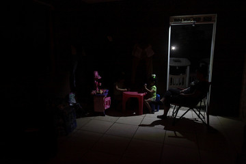 Children play next to their mother at their home after Hurricane Maria hit the island and damaged the power grid in September, in Vega Alta