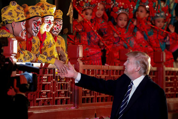 U.S. President Donald Trump shakes hands with opera performers at the Forbidden City in Beijing