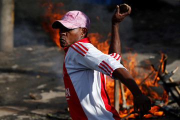 An opposition supporter throws a stone during a protest in the slum area of Mathare in the capital Nairobi