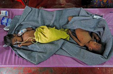 Ruaida Begum, 3, suffering from severe malnutrition, and her brother Nurul Amin, 1, suffering from pneumonia, lie on a bed at a diarrhoea treatment centre in Kutupalong refugee camp near Cox's Bazar