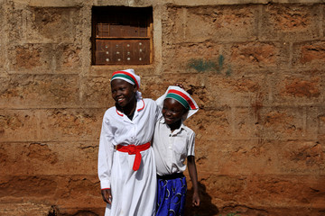 Girls smile at the beginning of a Sunday service outside of an African Divine Church near the slum area of Korogocho in the capital Nairobi
