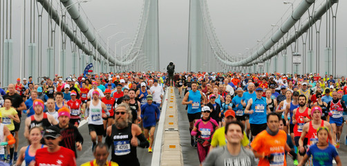 A photojournalist stands on the center divider as the first wave of runners make their way across the Verrazano-Narrows Bridge during the start of the New York City Marathon in New York