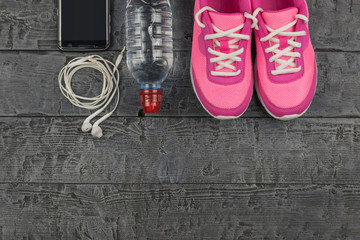 Beautiful pink sneakers, headphones, water and apples on a wooden dark floor. View from above.