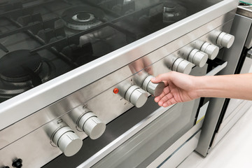 Woman's Hands adjusting heat button on oven machine