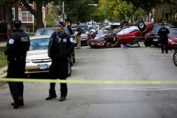 Chicago Police officers investigate a crime scene after a motorist was shot in the head and lost control of his vehicle along the 5300 block of west Monroe Street in Chicago, Illinois