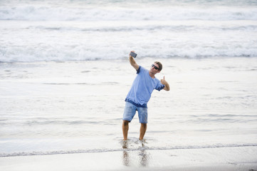 young attractive and happy Caucasian 30s man having fun at Asian beach taking selfie picture with mobile phone smiling excited in holiday