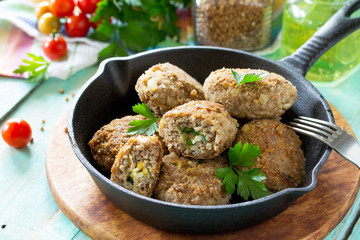 Homemade meatballs with buckwheat and egg stuffing. Cast-iron frying pan with delicious fried cutlets, fresh herbs and vegetables on the kitchen table.