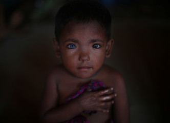 Refugee child who fled Myanmar two-months ago listens to singing at Kutupalong refugee camp near Cox's Bazar